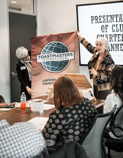 Nancy Ducket and Hallie Adams unveil the LAVIDGE Ad Libs Toastmasters banner at a charter and officer installation ceremony Feb. 5, 2020.