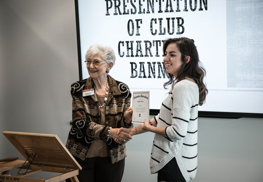 Distinguished Toastmaster Hallie Adams presents Courtney Vasquez with the LAVIDGE Ad Libs Charter certificate.